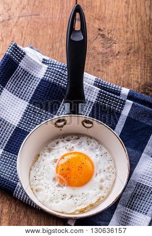 Egg. Fried egg. Chicken egg. Close up view of the fried egg on a frying pan. Salted and spiced fried egg.