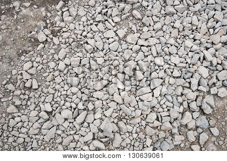Small dusty grey rocks on dirt road