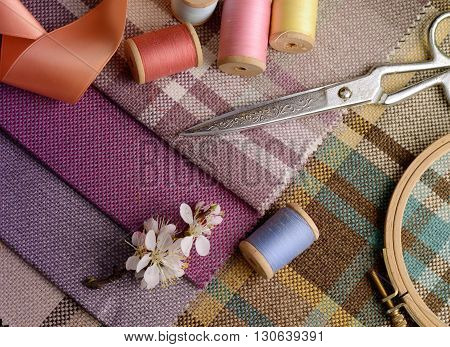 sewing supplies, needles, scissors on the colorful gunny textile background. Photo in gentle pastel colors