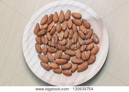 Some almonds in a wooden bowl view from above