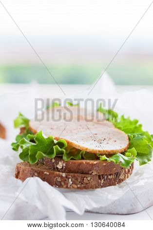 Homemade tasty sandwich with salad leaves and ham on a cutting board on a kitchen background with place for text selective focus