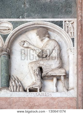 LUCCA, ITALY - JUNE 06, 2015: January, detail of the bas-relief representing the Labor of the months of the year, portal of the Cathedral of St Martin in Lucca, Italy, on June 06, 2015