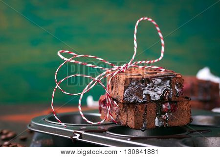 Homemade chocolate sweet brownies cakes with chocolate sauce or syrup on a dark background horizontal with place for text