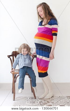 Pregnant woman 30 year old in colorful dress full boby in studio stands and looks at her  2 year old daughter, who is sitting on a chair and looking at the camera , smiling askance, sly