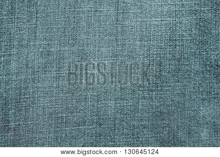 the textured background from rough cotton material or denim of pale indigo color