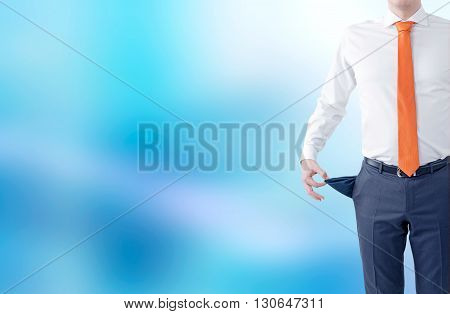 Unemployment concept with businessman showing empty pockets on abstract blue background