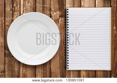 Empty plate and cookbook on wooden table