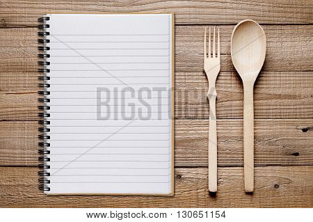 Cookbook spoon and fork on wooden table top view