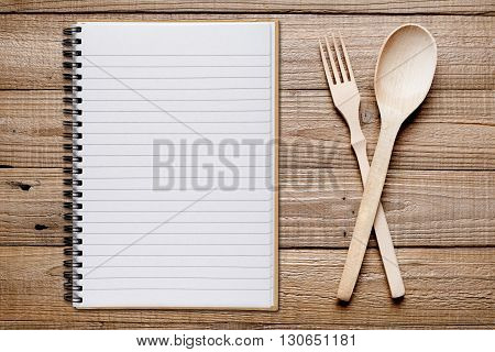 Cookbook fork and spoon on wooden table top view