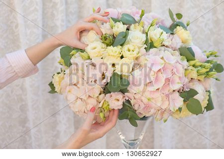 Florist making beautiful bouquet of flowers. Hydrangea, Lisianthus, Eucalyptus, Rose, Peony.