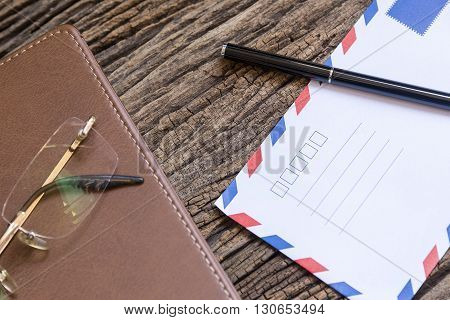 the envelop and the pen on the wooden background table with the note book