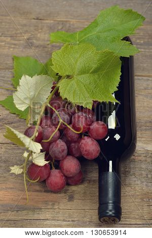 Bottle of wine and grapes on a wooden background