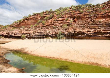 Natural landscape of red and white banded tumblagooda sandstone bluff in the valley of the Murchison River gorge in Kalbarri National Park with native plants under a blue sky with clouds in Western Australia.