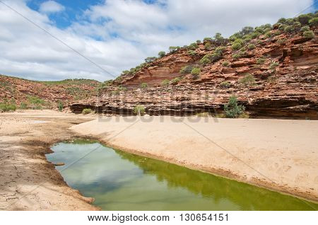 Minimal water and red tumblagooda sandstone cliffs in the valley of the Murchison River gorge in Kalbarri National Park with native plants under a blue sky with clouds in Western Australia.