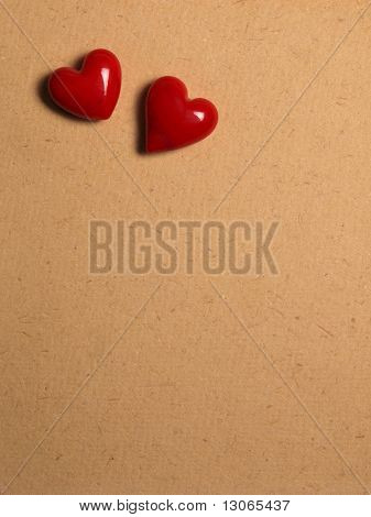 2 red hearts on hand-made paper