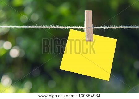the sticky note hanging on the clothesline with the garden background
