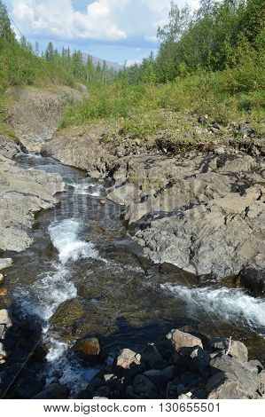Mountain stream on the Putorana plateau. Summer mountain landscape fast stream in a stone channel.