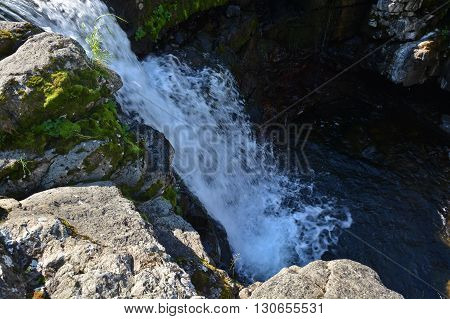 Waterfall on the Putorana plateau. Summer mountain landscape decorated by a waterfall.