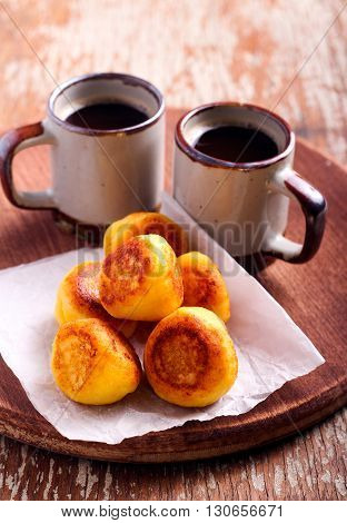 Vanilla ricotta fritters and cups of coffee on board