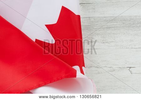 Canadian Flag Folded On White Rustic Wooden Table