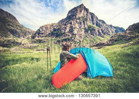 Man Traveler with camping equipment mat and tent outdoor Travel Lifestyle concept rocky mountains landscape on background Summer adventure vacations