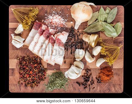 Pieces of lard and spice on a wooden chopping board