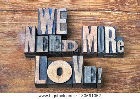 we need more love exclamation made from mixed wooden letterpress type on vintage wooden background