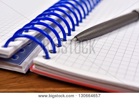 note pad with pen on wooden table close up