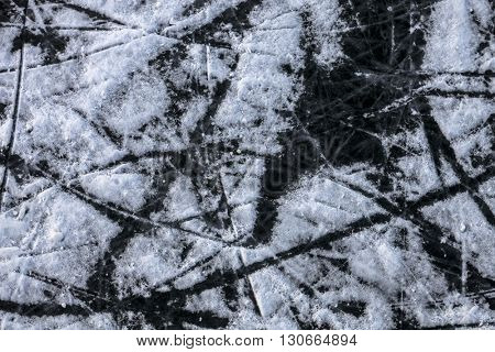 Background of ice surface with skates scratches in open rink