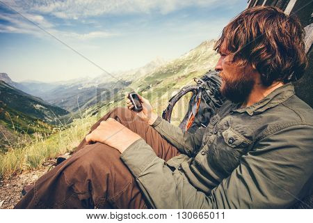 Bearded Man with gps navigator tracker relaxing alone Travel Lifestyle concept mountains and clouds on background Summer adventure vacations outdoor