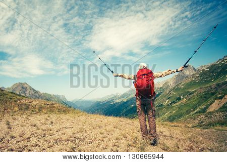 Happy Woman Traveler with backpack hands raised trekking poles enjoying mountains landscape Travel Lifestyle concept adventure vacations