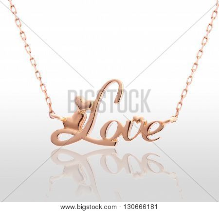 Gold pendant with the inscription love. Isolated white background.