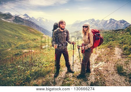 Happy Couple Man and Woman Travelers with backpacks hiking Travel Lifestyle and family love concept mountains landscape on background