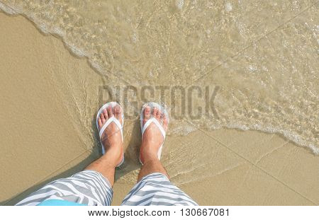 White flipflop sandals on sea beach, sand