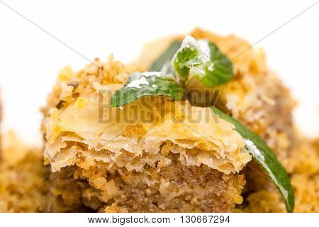 Delicious oriental dessert baklava covered with grated walnuts. Macro. Photo can be used as a whole background.