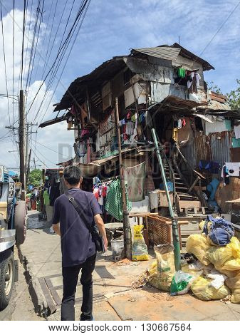 Manila Philippines - July 19 2015 : A man walks by a slum wooden house in Makati district Manlia
