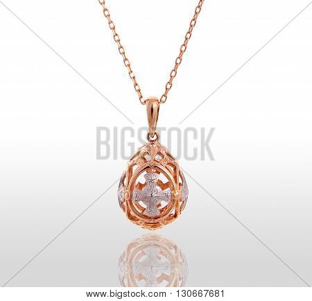 Gold pendant in the form of Easter eggs. Isolated white background.
