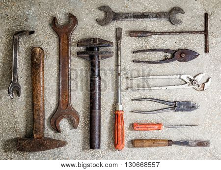 Old rusty tools arranged on the floor