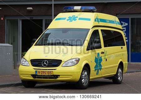 Almere, The Netherlands - May 21, 2016: Yellow Dutch Mercedes Vito Ambulance  parked bij the side of the road. Nobody in the vehicle.