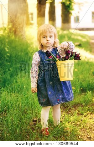 Child With Yellow Basket Of Purple Tulip Flowers In Spring Outdoors