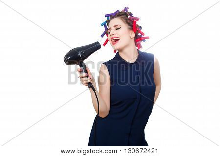 Isolated photo of young singing woman in curler with hairdryer.