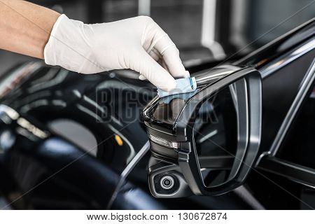 Car detailing series : Closeup of hand coating black car side mirror