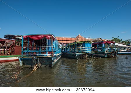 Tourist boats standing on a jetty in Siem Reap river. Siem Reap is a resort town located on the banks of Siem Reap and is gateway to Angkor Wat. Boat ride is a must-do activity here.