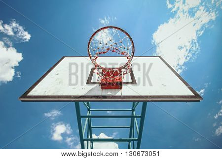 under the basketball ring and blue sky background