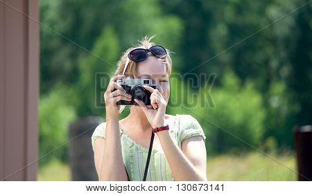 Girl photographs on film cameras on a sunny summer day