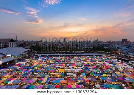 Aerial view, multiple colours flea market roof top with dramatic sky background after sunset