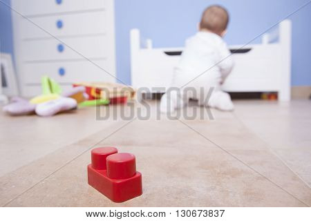 9 month baby boy playing with plastic building blocks. Selective focus