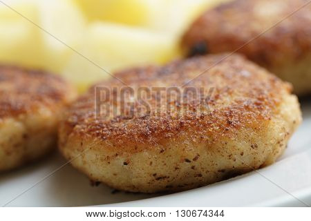 prepared fried fish cakes with boiled potatoes, shallow focus