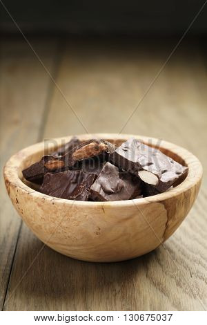 homemade chocolate with almonds in wood bowl, on wood table