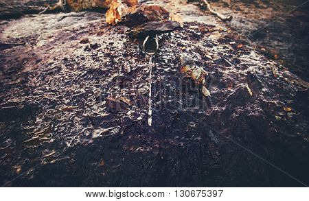 Mineral water well in Abkhazia mountains on rusty rocky background